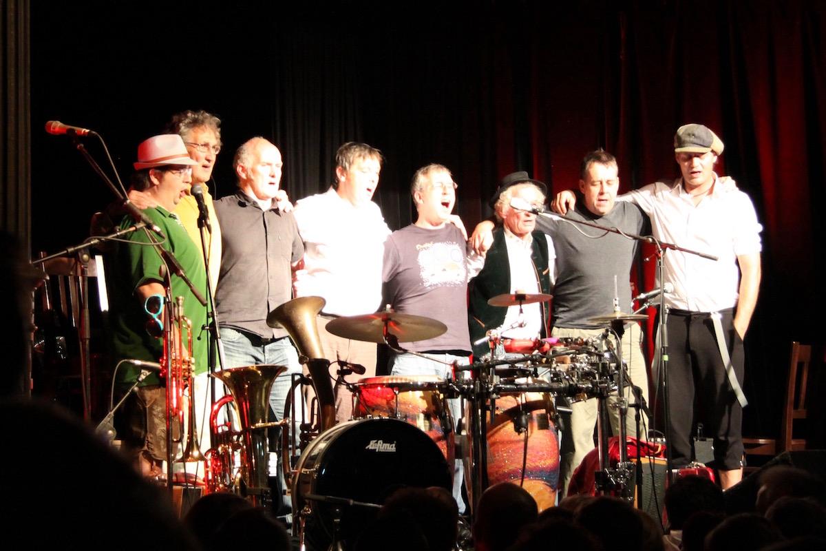 Da Huawa, da Meier und I und Na Ciotogi stehen Arm in Arm hinter dem Schlagzeug und singen The Auld Triangle