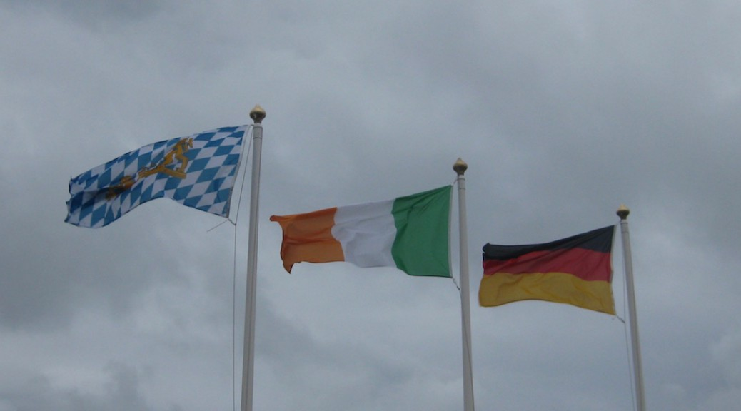 The Bavarian, Irish and German flag in front of a cloudy sky