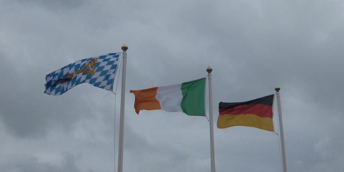 Die bayrische, irische und deutsche Flagge vor einem bewölkten Himmel