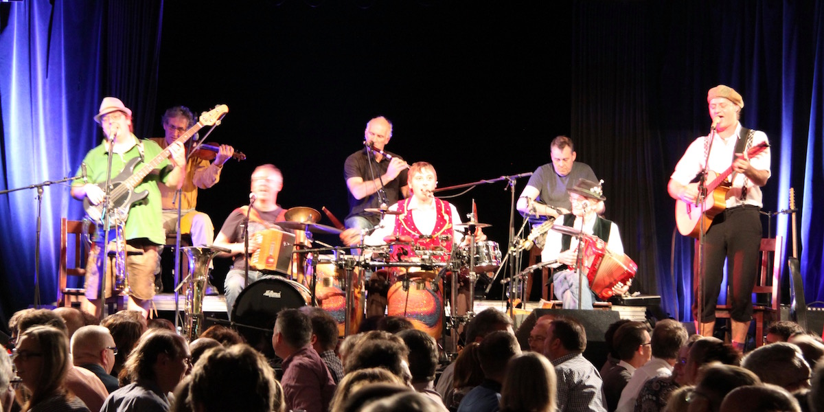The eight musicians of Da Huawa, da Meier und I and Na Ciotogi are standing and sitting on the stage playing an Irish-Bayrisch song