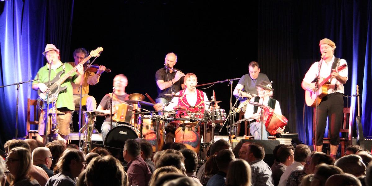 Die acht Musiker von Da Huawa, da Meier und I und Na Ciotogi stehen und sitzen auf der Bühne und spielen ein Irish-Bayrisch Lied