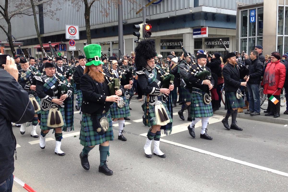 Schottische Pipe Band in traditionellem Outfit in schwarz, grün und blau.
