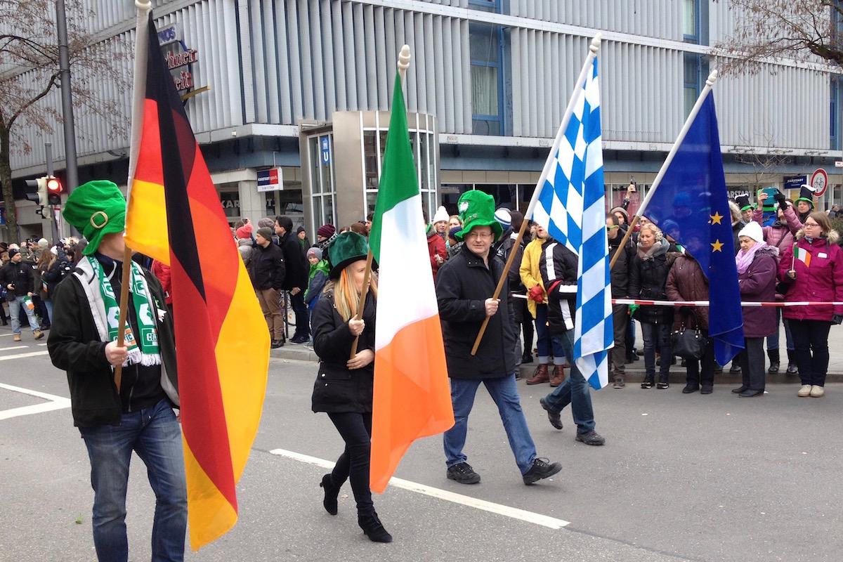 Die Flaggen von Deutschland, Irland, Bayern und Europa werden von vier Menschen an der Spitze der Parade getragen.