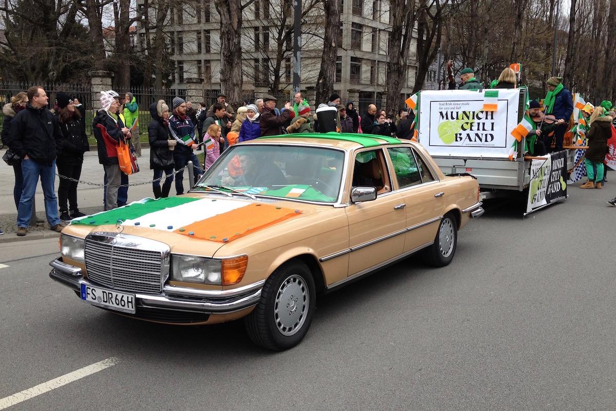Mercedes mit irischer Flagge auf der Motorhaube zieht einen Anhänger mit der Munich Ceili Band.