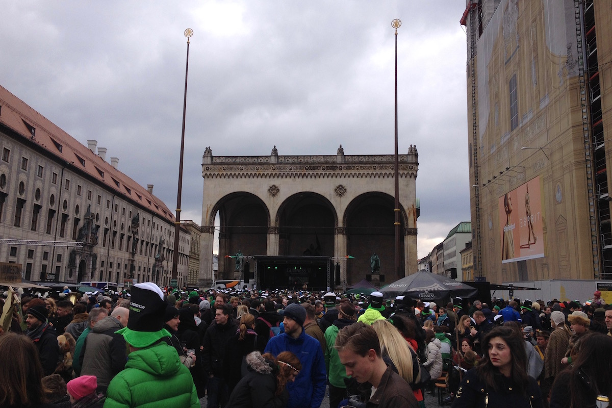 Lots of people are standing and sitting on Odeonsplatz and celebrate St. Patrick.