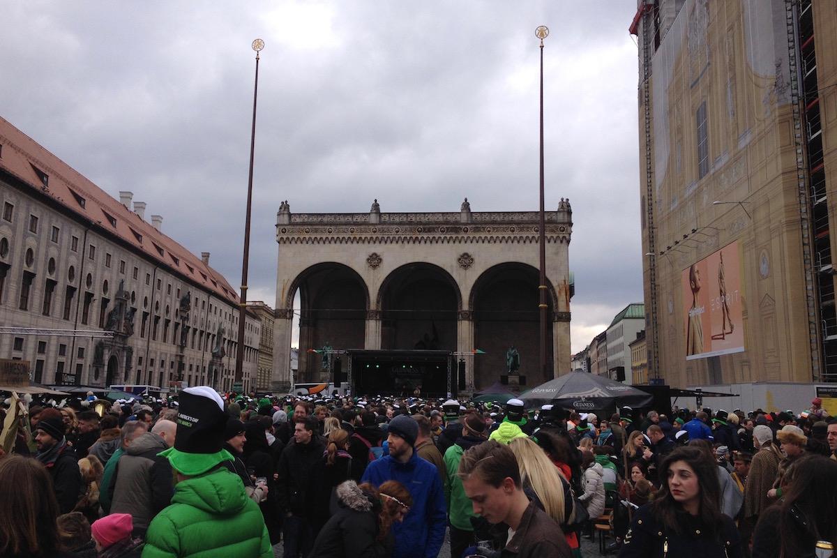 Viele Menschen stehen und sitzen auf dem Odeonsplatz und feiern St. Patrick.
