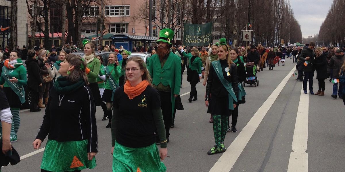 The Emerald Dancers in schwarz und grün gehen und tanzen die Leopoldstraße herunter.