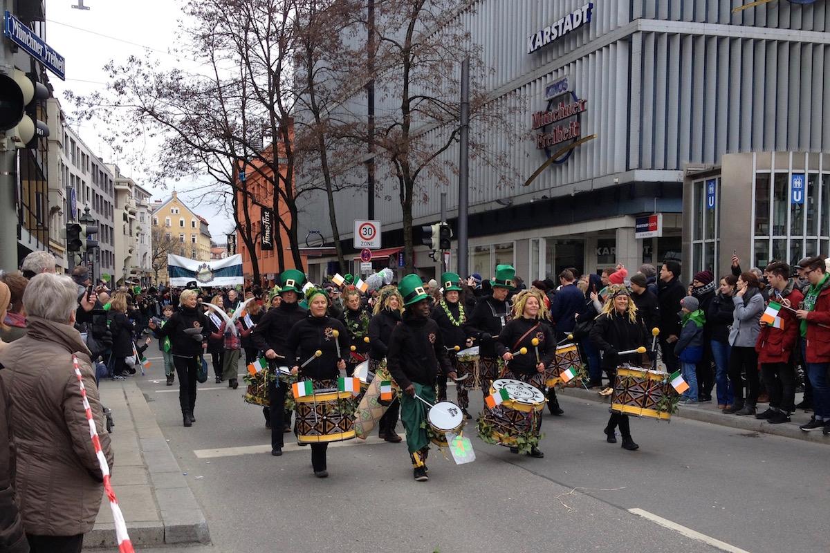 Afro-brasilianische Gruppe trägt ihre Trommeln. Einige tragen grüne Hüte.