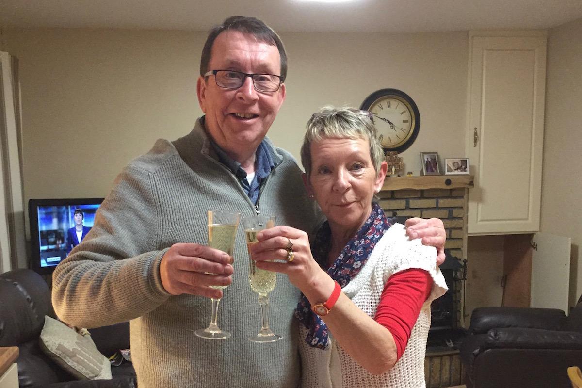 Father Ray Kelly und seine Schwester Regina stehen in einem Wohnzimmer und halten zwei Gläser Sekt in den Händen.
