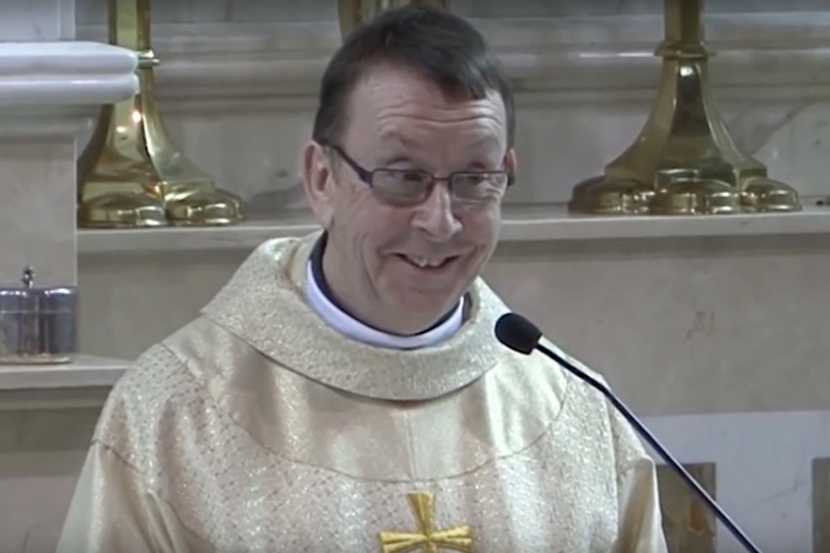 Father Ray Kelly sings Hallelujah and smiles.