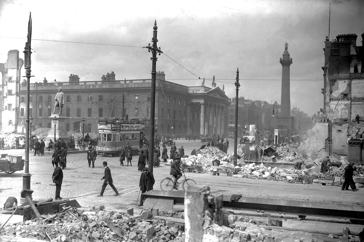 Black and white photograph of Abbey Street and Sackville Street with statue of William Smith O'Brien, the General Post Office and Nelson's Pillar. You can see piles of rubble, pedestrians, a few cars and a tram.