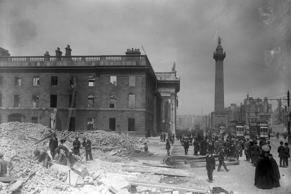 Schwarz-Weiß-Foto vom bombardierten General Post Office, Sackville Street und Nelson's Pillar. Man sieht Trümmerberge vor dem General Post Office und viele Fußgänger und Trambahnen auf der Sackville Street.