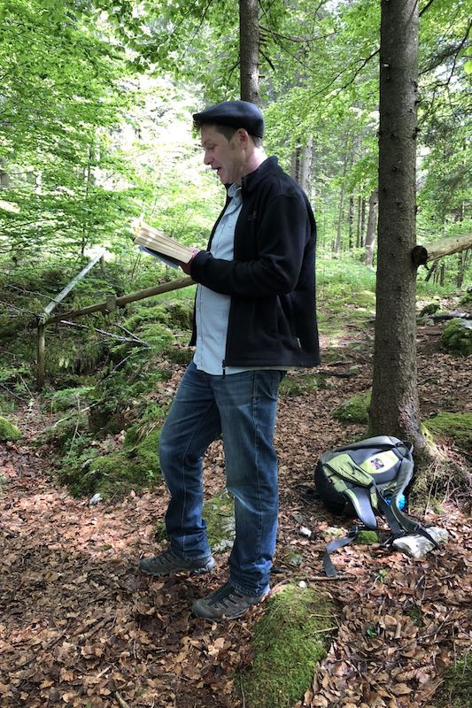 Oliver Pötzsch stands in the forest at the Döttenbichl and reads from his book The Play of Death