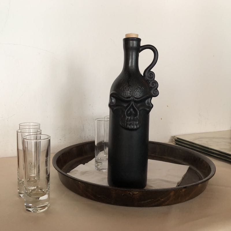 Black bottle with skull on tray and glasses
