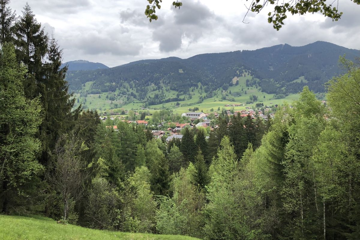 Some houses of Oberammergau between trees in the foreground and mountains overgrown with trees in the background