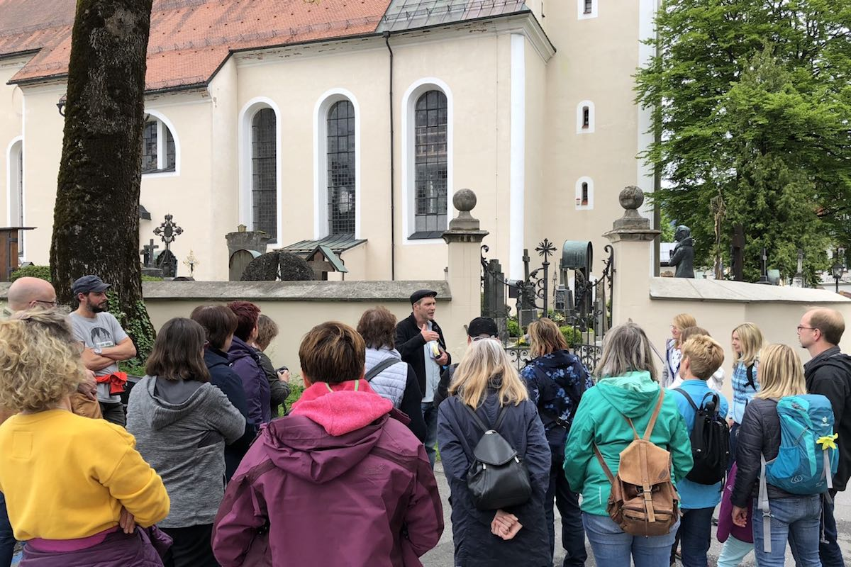 Oliver Pötzsch stands in front of the cemetery wall and explains the origin of the Passion play to the group