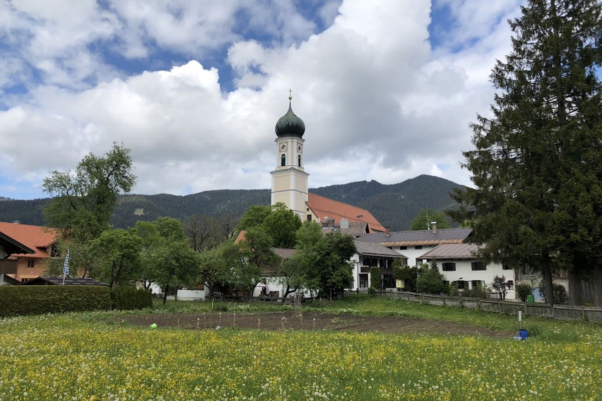 Church that towers above a yellow-white flowery meadow, the roofs of Oberammergau and the mountains behind it