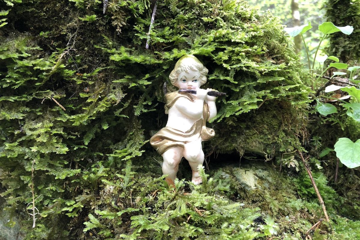 White figure of an angel with a flute standing in an area overgrown with moss