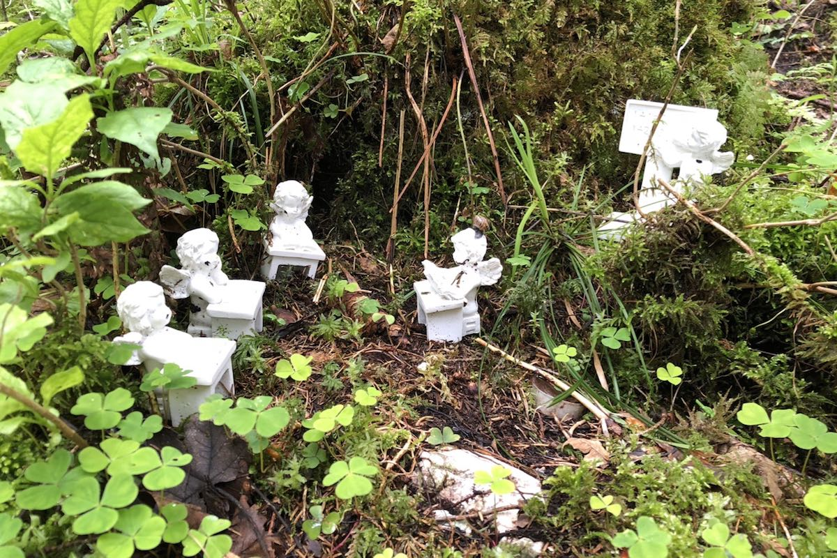 Four white figures of angels sitting at their little tables and one standing at a board in an area with shamrocks and moss