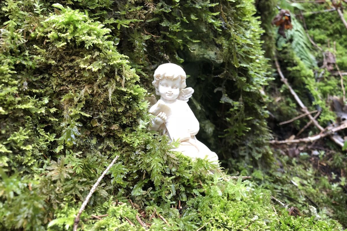 White figure of an angel sitting in an area overgrown with moss